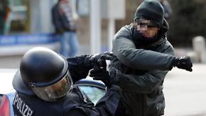 ARCHIV - Ein gewalttätiger Demonstrant schlägt am 26.03.2011 in Lübeck (Schleswig-Holstein) einen Polizeibeamten nieder. Foto: Carsten Rehder/dpa (zu dpa: «Wenn Gewalt unter die Haut geht - Angriffe auf Polizisten nehmen zu» vom 27.04.2016) +++(c) dpa - Bildfunk+++