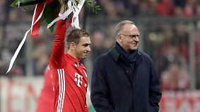 Bayern's Philipp Lahm waves on the field with flowers besides Bayern CEO Karlheinz Rummenigge prior to the German Soccer Cup match between FC Bayern Munich and VfL Wolfsburg at the Allianz Arena stadium in Munich, Germany, Tuesday, Feb. 7, 2017. (AP Photo/Matthias Schrader)