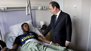 In this photo dated Tuesday, Feb. 7, 2017, provided by Le Parisien, France's President Francois Hollande, right, stands next to alleged victim, identified only by his first name, Theo, at Robert Ballanger hospital in Aulnay-sous-Bois, north of Paris, France. Violence in suburbs northeast of Paris have now spread to at least five towns, erupting after a young black man was allegedly sodomized with a police officer's baton last week, during an identity check. One officer was charged Sunday with aggravated rape and three others were charged with aggravated assault. (Arnaud Journois/Le Parisien via AP)