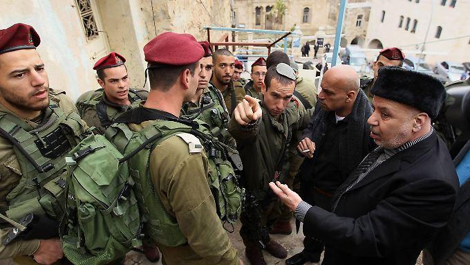 Palästinensische Männer diskutieren auf einer Straße in Hebron mit israelischen Soldaten über den Zugang zu ihrem Land.