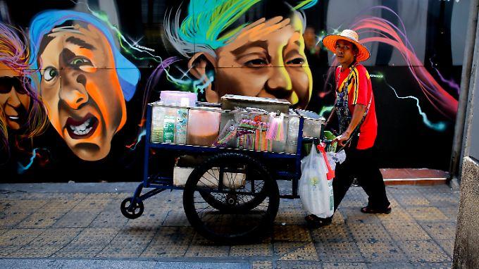 Ein Straßenhändler schiebt seine mobile Küche durch die Straßen Bangkoks.