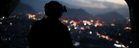 Ein US-Soldat beobachtet aus der Heckklappe eines Hubschraubers heraus die Lichter des abendlichen Kabul.