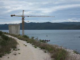 Ein Baukran und ein unfertiger Brückenpfeiler auf der Baustelle.