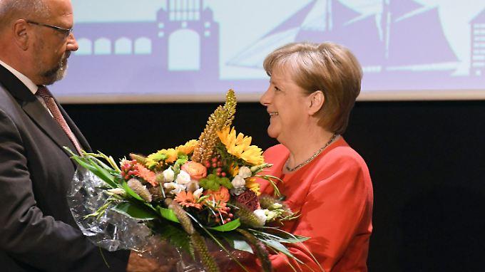 Am Montag erhielt Merkel auf dem Sommerempfang der IHK Rostock einen Blumenstrauß zu ihrem 63. Geburtstag.