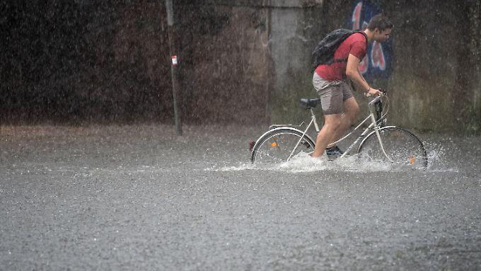 Ein Radfahrer in Köln kämpft sich durch die Fluten.