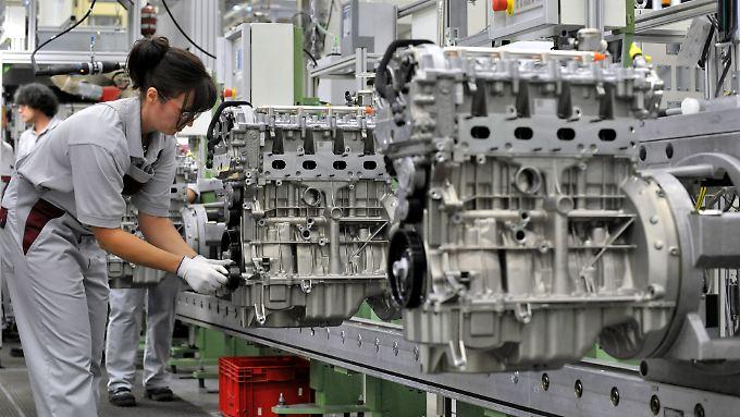 Beim Automobilzulieferer MDC Power im thüringischen Kölleda montiert eine Mitarbeiterin einen Vierzylinder-Benzinmotor.