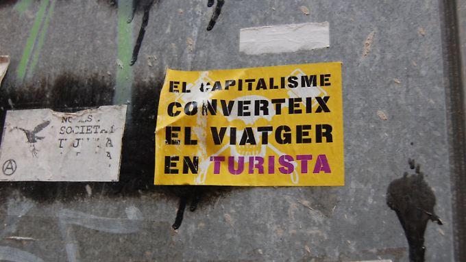 """Aufkleber mit der Aufschrift """"El Kapitalisme converteix el Viatger en Turista"""" (""""Der Kapitalismus verwandelt den Reisenden in einen Touristen"""") in Palma de Mallorca."""