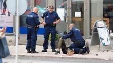 Die Polizei überwältigt den Messerstecher.