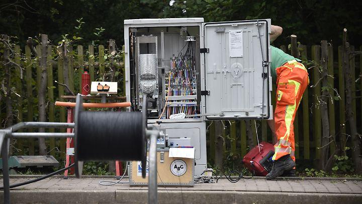 Ein Techniker installiert in Brumby in Sachsen-Anhalt ein neues Glasfaserkabel in einem Verteilerkasten. Vor allem die neuen Bundesländer sind mit der Technologie noch nicht weit erschlossen.