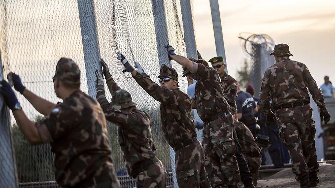 In Röszke an der Grenze zwischen Serbien und Ungarn errichten ungarische Soldaten im September 2015 einen Zaun.
