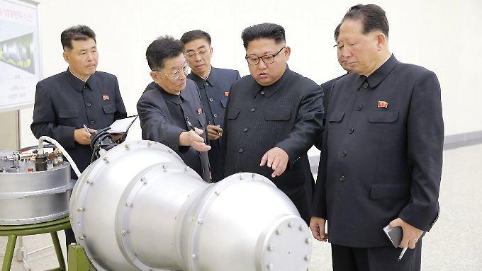 Kürzlich veröffentlichte Bilder des nordkoreanischen Regimes sollen Diktator Kim (M.) mit einer Wasserstoffbombe zeigen.