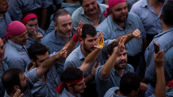 Männer singen in Barcelona die offizielle Nationalhymne Kataloniens, bevor sie eine als Castell bezeichnete Menschenpyramide bilden. Eine Woche vor dem umstrittenen Referendum über die Loslösung von Spanien haben Separatisten in ganz Katalonien Wahlzettel verteilt.
