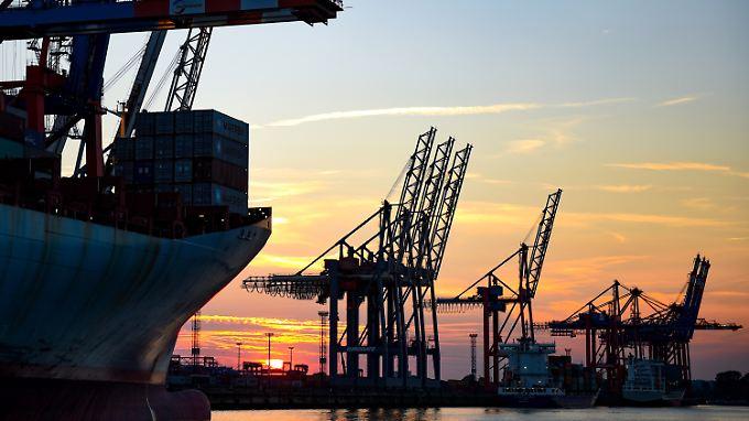 Sonnenuntergang im Hamburger Hafen hinter Kränen zur Containerverladung.