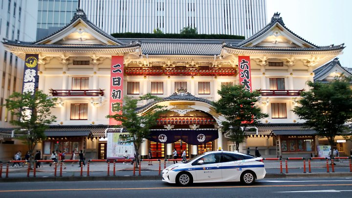Straßenszene in Tokio: Ein Hybrid-Taxi von Toyota fährt vor dem Kabuki-Theater vor.
