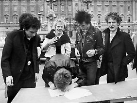 März 1977: Die Sex Pistols unterschreiben ihren Vertrag mit EMI, vor dem Buckingham Palace. Rechts Manager Malcolm McLaren.