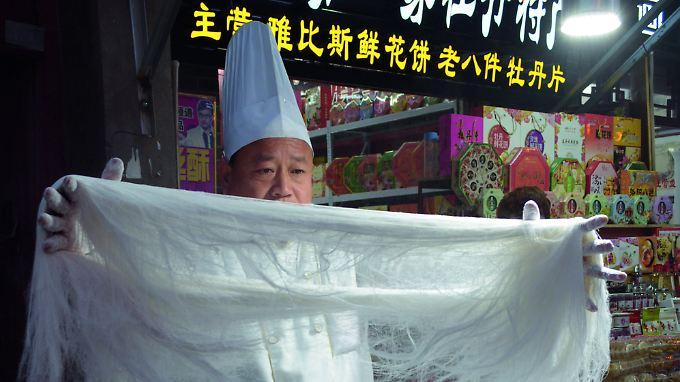In den Garküchen Chinas kann man meist den Köchen bei der Arbeit zusehen: beim Nudeln ziehen, Gemüse schnippeln oder beim Rühren im Wok.