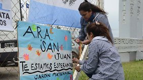 """""""Wir warten auf Dich"""", steht auf diesem Plakat, das zwei Frauen am Zaun des Stützpunktes befestigen."""