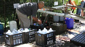 Vor einer natürlichen Quelle drängeln sich zahlreiche Bewohner, um Wasserkanister aufzufüllen.