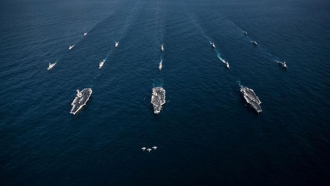 Drei F-18-Kampfjets begleiten die Flugzeugträger USS Ronald Reagan, USS Theodore Roosevelt und USS Nimitz sowie deren Begleitschiffe im November auf ihrer Fahrt durch den Westpazifik.