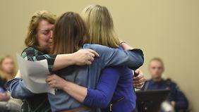 Zeugin Krista W. (r.) umarmt nach ihrer Aussage ihre Mutter (l.) und eine weitere Person.