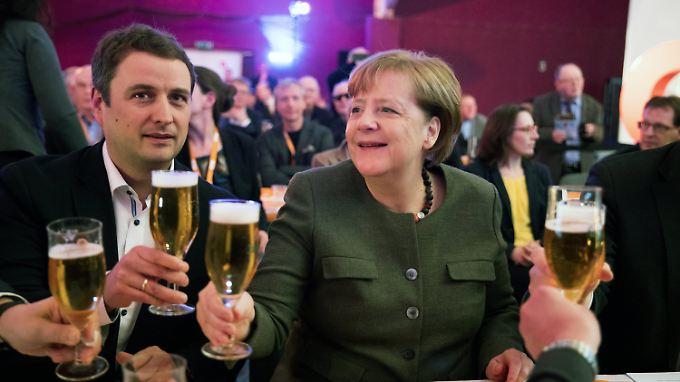 Merkel und Landeschef Vincent Kokert mit den Grundutensilien des politischen Aschermittwochs.