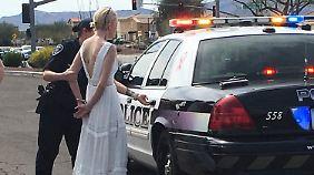 In Handschellen verfrachtet eine Polizistin die Braut in den Streifenwagen.