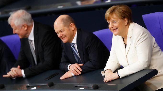 Eingerahmt vom neuen Innenminister Horst Seehofer und Bundeskanzlerin Angela Merkel sitzt der frisch vereidigte Finanzminister Olaf Scholz auf der Regierungsbank.