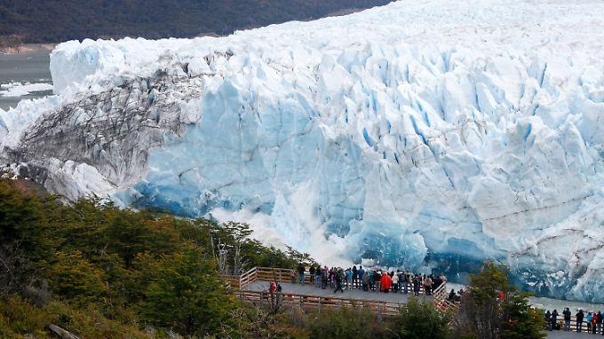 Menschen bestaunen den Perito-Moreno-Gletscher in Argentinien, als die Gletscherfront abbricht.