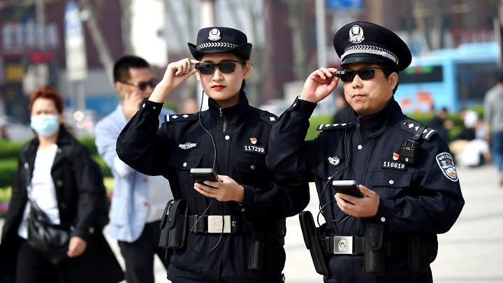 """Chinesische Polizisten setzen in der Henan-Provinz ihre """"intelligenten"""" Sonnenbrillen ein, die dank künstlicher Intelligenz und Minibildschirmen verdächtige Aktivitäten in den Gläsern anzeigen."""