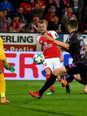 Der Mainzer Daniel Brosinski flankt - und gleich lenkt der Freiburger Marc Oliver Kempf den Ball mit dem ausgestreckten linken Arm ab.