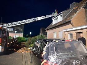 Abgedeckte Dächer, zerschmetterte Scheiben: Bis in die Nacht hinein arbeiten Helfer daran, die gröbsten Schäden notdürftig abzusichern.