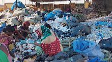 Am Rande von Neu Delhi trennen Arbeiter eines Mülldepots den Plastikabfall per Hand.