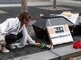 Eine Aktivistin legt Blumen neben einem Sarg vor dem Bundesinnenministerium nieder.