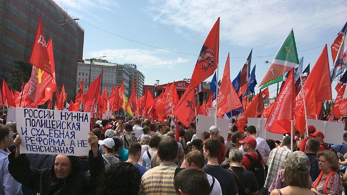 """Ein Demonstrationsteilnehmer in Moskau hält ein Schild mit der Aufschrift """"Russland braucht eine Polizei- und Gerichtsreform, keine Rentenreform""""."""
