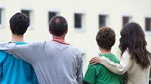 Eine syrische Familie sitzt vor einem Asylwohnheim in Brandenburg.