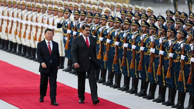 Während die OAS bereits mit einer Militäraktion zu seinem Sturz liebäugelt, wird Maduro in China mit allen Ehren als Staatsgast empfangen.
