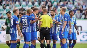 Wolfsburgs Malli schnappt sich den Ball, während sich Schiedsrichter Dingert den fassungslosen Berlinern erklärt.