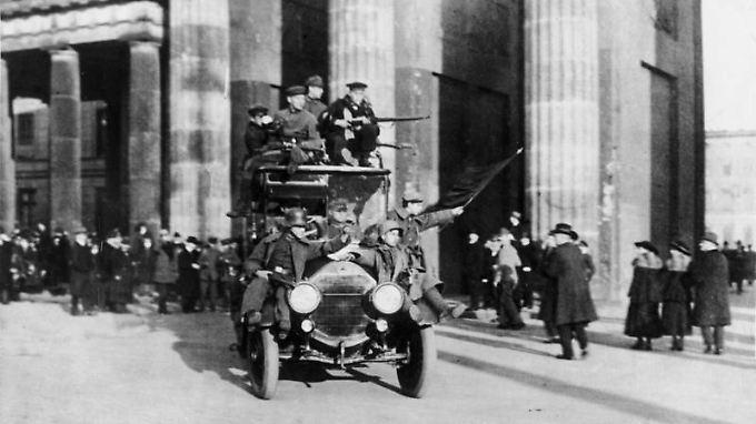 Revolutionäre fahren am 9. November 1918 durch das Brandenburger Tor.