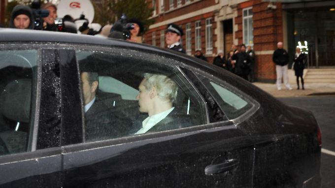 Assange in einem Wagen der Polizei.
