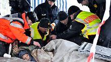 Der Rettungsdienst versorgt zwei Robin-Wood-Aktivisten, die auf der Castor-Transportstrecke an ein Gleis gekettet sind.