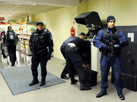 Unter umfangreichen Sicherheitsvorkehrungen bestücken Bankangestellte im ganzen Land die Geldautomaten.