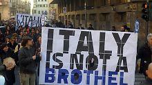"""Demonstranten mit einem Plakat: """"Italien ist kein Bordell""""."""