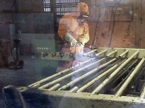 Handarbeit: Ein Arbeiter zerlegt alte Absperrgitter.