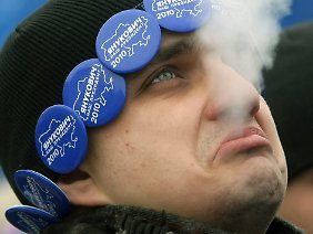Ein Anhänger des regierenden ukrainischen Präsidenten Janukowitsch raucht bei einer Kundgebung in Kiew.