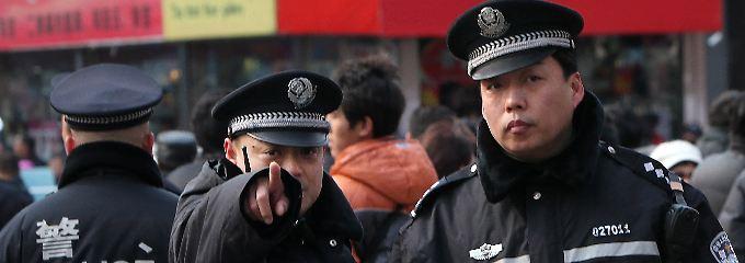 """Chinesische Polizisten zeigen auf Journalisten, die über eine Protestaktion der """"Jasmin Revolution"""" in Peking berichten wollen (Archivfoto vom 20.02.2011)."""