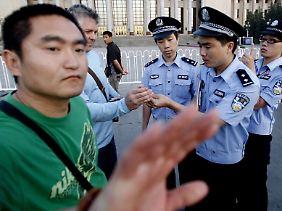 Ein chinesischer Polizist in zivil (l) hält Journalisten auf dem Tian'anmen-Platz davon ab die Kontrolle eines Kameramanns durch Polizei näher zu fotografieren