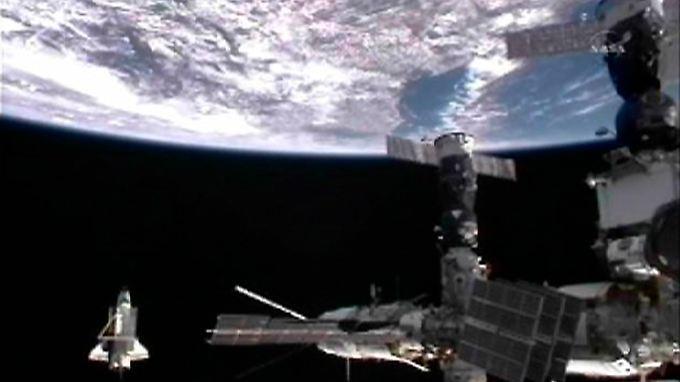 """Die """"Discovery"""", links unten, umrundet ein letztes Mal die internationale Raumstation ISS."""
