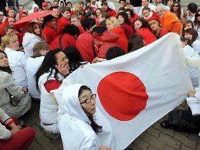 In Berlin bilden Menschen mit ihrer roten und weißen Kleidung die japanische Flagge nach.