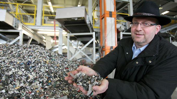 Adamec hält zerkleinerten Elektronikschrott in den Händen, der anschließend in alle einzelnen Rohstoffe getrennt wird.