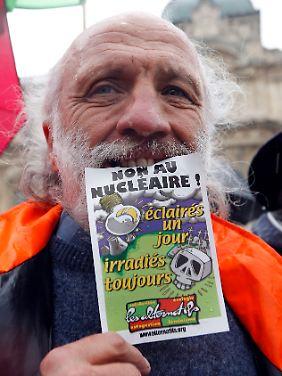 """Ein französischer Atomkraftgegner protestiert in Marseilles: """"Nein zur Atomkraft! Einen Tag erleuchtet, verstrahlt für immer""""."""